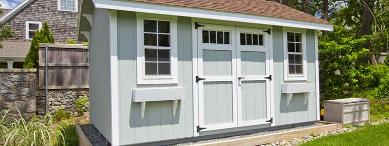 Light blue shed with barn doors and windows