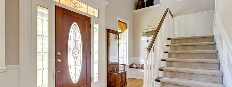 entryway of home with stair leading up and many ways for natural light to enter the area