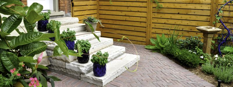 brick patio with concrete steps and potted plants on each step