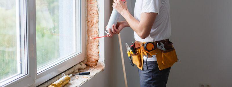 person using spray insulation to fill air gaps around window