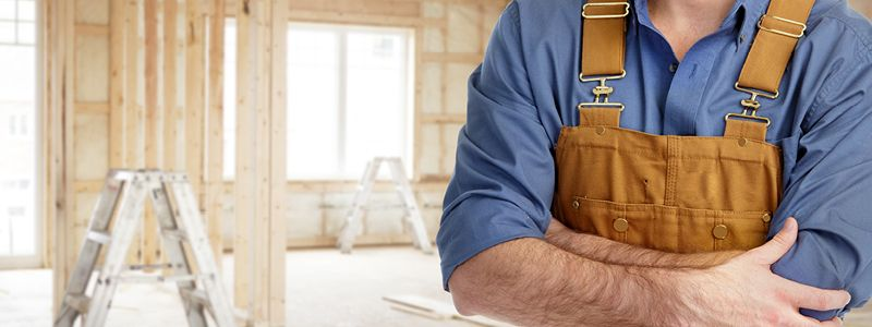 man wearing bib overalls standing with crossed arms in home under construction