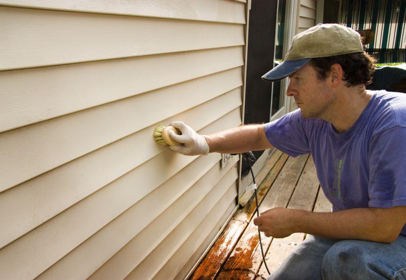 man washing house's siding with brush